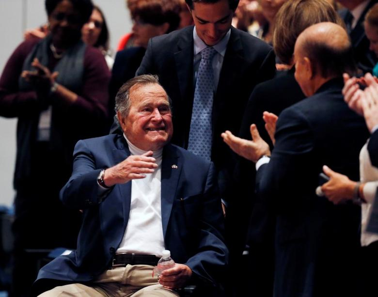 Former United States President George H. W. Bush is brought into the auditorium where his son Former United States President George W. Bush speaks about his new book titled ''41: A Portrait of My Father'' at the George Bush Presidential Library Center in College Station, Texas November 11, 2014.  REUTERS/Bob Daemmrich/Pool