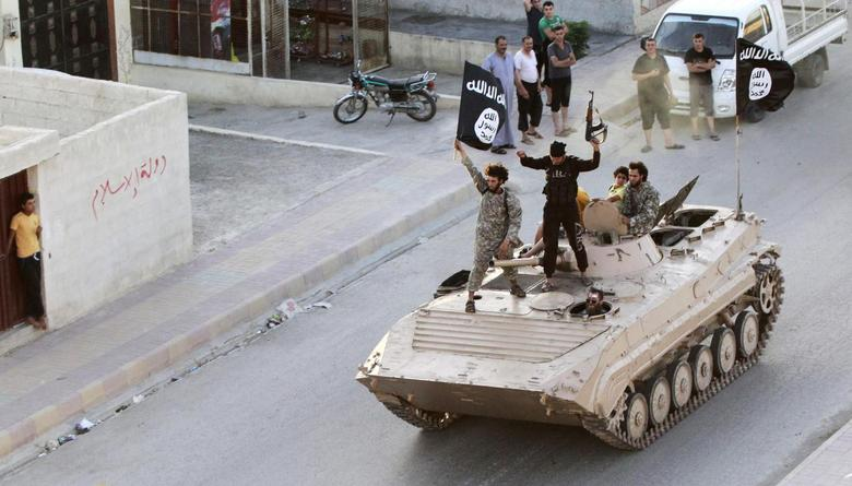 Islamic State fighters take part in a military parade along the streets of northern Raqqa province, June 30, 2014.  REUTERS/Stringer
