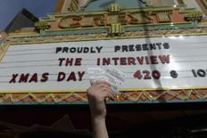 """Tickets for the film """"The Interview"""" is seen held up by theater manager Donald Melancon for the media at Crest Theater in Los Angeles, California December 24, 2014.  REUTERS/Kevork Djansezian"""