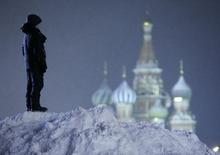 Мальчик на вершине сугроба на Красной площади в Москве 25 декабря 2014 года. Конец год в Москве будет морозным, свидетельствует усреднённый прогноз, составленный на основании данных Гидрометцентра России, сайтов intellicast.com и gismeteo.ru. REUTERS/Sergei Karpukhin