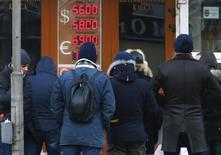 Очередь в обменный пункт в Москве 29 декабря 2014 года. Рубль удерживается в положительной зоне на последней торговой сессии чрезывычайно сложного для российской валюты 2014 года, решив проигнорировать снижение нефтяных котировок с помощью продаж валюты крупными госкорпорациями. REUTERS/Sergei Karpukhin