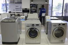 Samsung washing machines are seen as an employee inspects refrigerators at a Samsung display store in Johannesburg, October 3, 2013. REUTERS/Siphiwe Sibeko