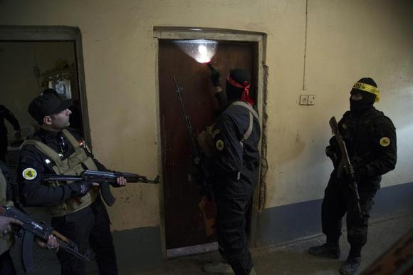 Fighters from the Shi'ite Kata'ib Imam Ali (Imam Ali Brigades) militia search a house after taking control of a village from Islamist State militants, on the outskirts of Dhuluiya, north of Baghdad December 29, 2014.  REUTERS/Stringer