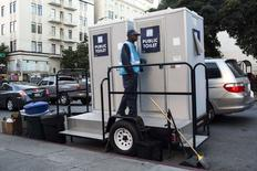 An attendant stands outside two portable toilets in the Tenderloin District in San Francisco, California December 30, 2014.  REUTERS/Stephen Lam