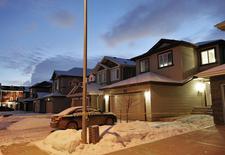 Police cordon tape surrounds a house (R, with lights on) where seven people were found dead, in one of three separate crime scenes, in north Edmonton, Alberta, December 30, 2014. REUTERS/Dan Riedlhuber