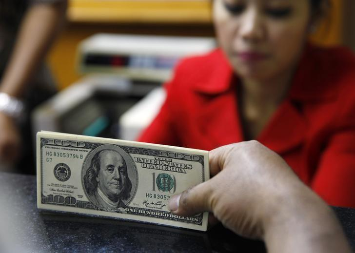 A money changer holds a stack of U.S. bills in Jakarta, August 29, 2013. REUTERS/Beawiharta