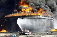 Bomberos trabajan para apagar un incendio en un depósito petrolero en Es Sider. Imagen de archivo, 19 diciembre, 2014.  Libia extinguió un incendio en un depósito petrolero en Es Sider, el mayor puerto petrolero de Libia, que se extendió por casi una semana, dijeron funcionarios el viernes.  REUTERS/Stringer