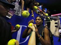 Singapore Slammers' Serena Williams of the U.S. signs autographs after her match against Manila Mavericks' Kirsten Flipkens of Belgium at the International Premier Tennis League (IPTL) in Singapore December 2, 2014. REUTERS/Edgar Su