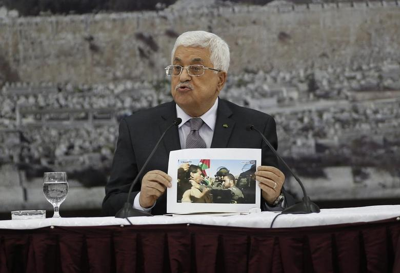 Palestinian President Mahmoud Abbas shows a picture of Palestinian minister Ziad Abu Ein as he is grabbed by an Israeli border policeman, during a meeting with the Palestinian leadership in the West Bank city of Ramallah December 10, 2014.  REUTERS/Mohamad Torokman