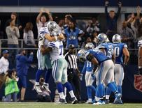 Dallas Cowboys quarterback Tony Romo (9) celebrates his winning touchdown pass with tackle Tyron Smith (77) against the Detroit Lions during the fourth quarter in the NFC Wild Card Playoff Game at AT&T Stadium.  Tim Heitman-USA TODAY Sports