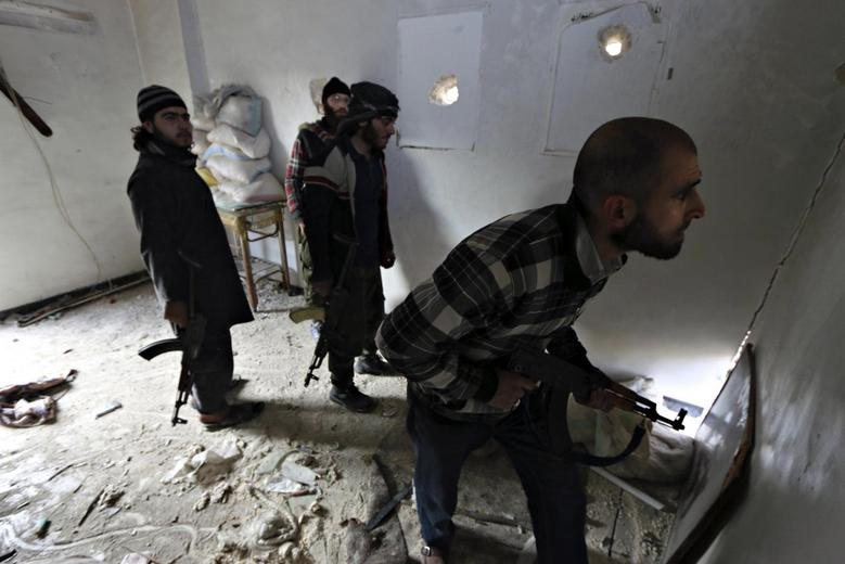 Rebel fighters stand in a room as one of them peeks out at the frontline against forces loyal to Syria's President Bashar al-Assad in the old city of Aleppo December 30, 2014. REUTERS/Abdalrhman Ismail