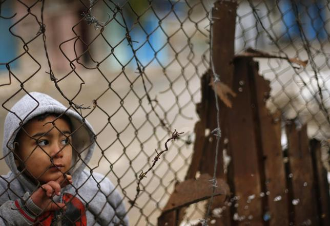 A Palestinian boy looks through a fence near his family's house (not seen), that witnesses said was damaged by Israeli shelling during a 50-day war last summer, in the east of Gaza City January 7, 2015.  REUTERS/Suhaib Salem
