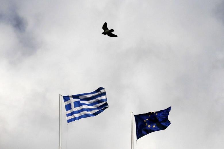 A Greek (L) and an EU flag flutter as a pigeon flies past in Athens January 6, 2015.   REUTERS/Alkis Konstantinidis