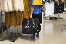 Una mujer sujeta una bolsa de Zara en el interior de uno de sus locales comerciales en Madrid. Imagen de archivo, 12 septiembre, 2014. La gigante minorista española Inditex anunció el jueves que abrirá más de una docena de sus tiendas de ropa Zara en Estados Unidos este año, incluyendo un local central en el área de SoHo en Nueva York.  REUTERS/Andrea Comas