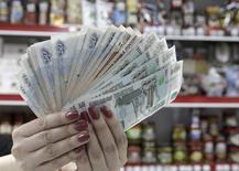 """Кассир показывает рублевые купюры в магазине в Ставрополе 7 января 2015 года. Рубль подешевел утром понедельника вслед за нефтяными котировками, а также на фоне риска снижения кредитного рейтинга РФ до """"мусорного"""" статуса уже на текущей неделе. REUTERS/Eduard Korniyenko"""