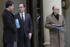 """Manuel Valls, François Hollande et Bernard Cazeneuve à l'Elysée. Le Premier ministre a évoqué lundi de premières pistes pour renforcer la lutte contre la menace terroriste en France, notamment la possibilité d'isoler des détenus déjà radicalisés des autres, tout en se montrant prudent sur l'idée d'un """"Patriot Act"""". /Photo prise le 10 janvier 2015/REUTERS/Philippe Wojazer"""