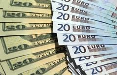 Банкноты доллара США и евро в Париже. 28 октября 2014 года. Доллар растет в понедельник, восстановившись после спада, вызванного неожиданно слабыми данными о зарплатах в США. REUTERS/Philippe Wojazer