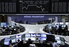 Traders are pictured at their desks in front of the German share price index DAX board at the Frankfurt stock exchange on January 12, 2015. REUTERS/Remote/Stringer