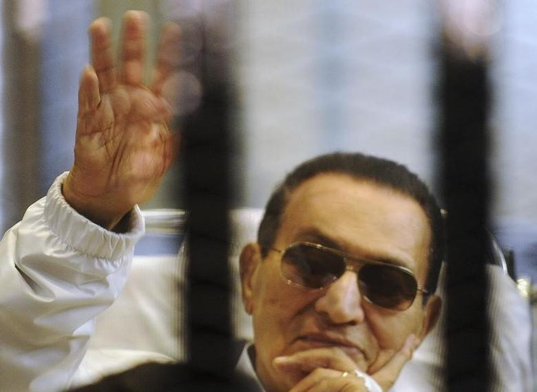 Former Egyptian President Hosni Mubarak waves to his supporters inside a cage in a courtroom at the police academy in Cairo April 13, 2013. REUTERS/Stringer