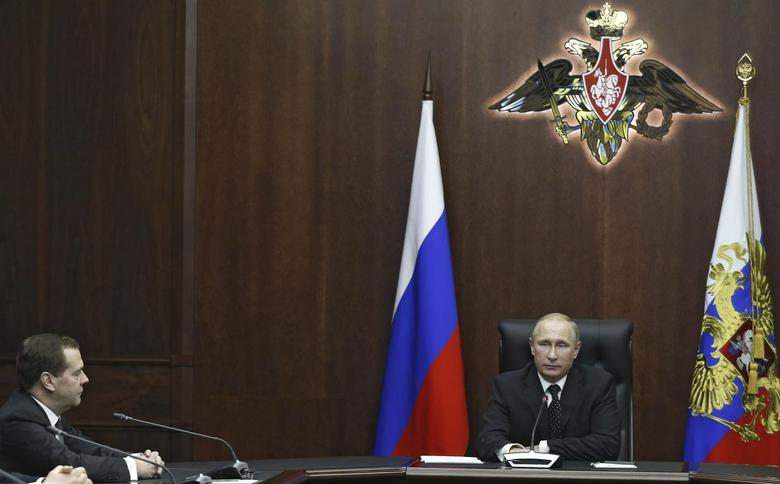 Russia's President Vladimir Putin (R) and Prime Minister Dmitry Medvedev attend a meeting of the Security Council at the Russian defense control center in Moscow, December 19, 2014. REUTERS/Alexei Druzhinin/RIA Novosti/Kremlin