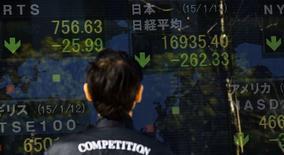 Мужчина у брокерской конторы в Токио. 13 января 2015 года. Азиатские фондовые рынки завершили торги вторника разнонаправленно под влиянием рынка нефти и местных факторов. REUTERS/Thomas Peter