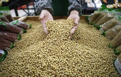 En la imagen, un empleado selecciona semillas de soja en un supermercado en Wuhan, provincia de Hubei. 14 de abril, 2014. China, el comprador de soja más grande del mundo, importó un récord de 8,53 millones de toneladas de soja en diciembre, lo que representa un alza de un 41,5 por ciento en el mes y de un 16,8 por ciento frente al récord anterior establecido en diciembre del año pasado, mostraron datos de aduanas el martes. REUTERS/Stringer