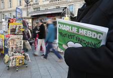 """Мужчина держит в руках еженедельник Charlie Hebdo рядом с газетным киоском в Ницце  14 января 2015 года. """"Аль-Каида"""" в Йемене взяла на себя ответственность за атаку на французский сатирический еженедельник Charlie Hebdo в видео на Youtube, где назвала поводом для нападения оскорбление пророка Мохаммеда. REUTERS/Eric Gaillard"""