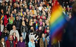 "People sing the Russian national anthem while raising rainbow flags in solidarity with the lesbian, gay, bisexual and transgender (LGBT) community of Russia, as part of a film project called ""Live and Let Love"", at the Stockholm Olympic Stadium October 6, 2013.  REUTERS/Erik Martensson/TT News Agency"
