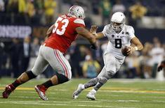 Oregon Ducks quarterback Marcus Mariota (8) avoids Ohio State Buckeyes defensive tackle Michael Bennett (53) in the 2015 CFP National Championship Game at AT&T Stadium. Mandatory Credit: Matthew Emmons-USA TODAY Sports