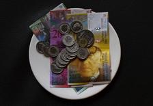 Купюры и монеты швейцарской валюты франк в ресторне в Цюрихе 21 мая 2013 года. Национальный банк Швейцарии в четверг отменил торговые ограничения для франка, после чего валюта упала ниже предела 1,20 за евро, установленного банком более трех лет назад. REUTERS/Michael Buholzer