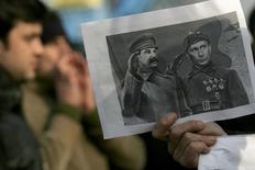 Участник акции протеста держит в руках листок с изображением Иосифа Сталина (слева) и Владимира Путина в Софии 18 января 2008 года. Власти Литвы намерены защитить своих граждан, снабдив их инструкциями на случай иностранного вторжения, возможность которого страны Балтии видят реальной на фоне действий России на Украине. REUTERS/Nikolay Doychinov