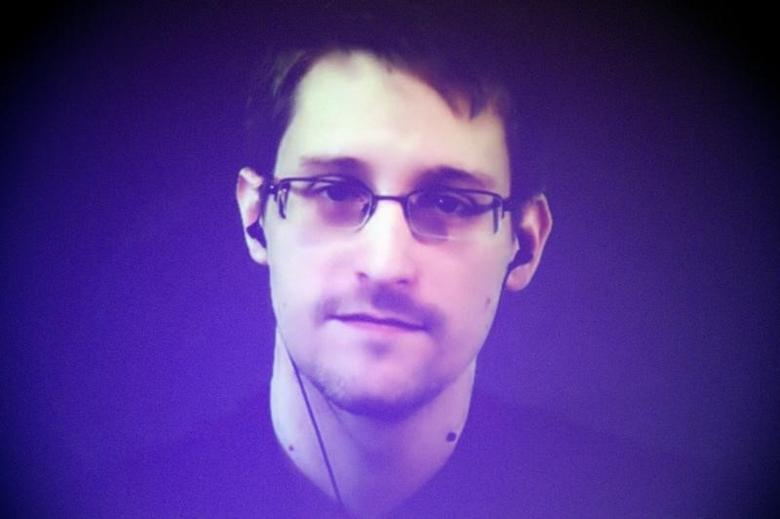 Former U.S. National Security Agency contractor Edward Snowden, who is in Moscow, is seen on a giant screen during a live video conference for an interview as part of Amnesty International's annual Write for Rights campaign at the Gaite Lyrique in Paris December 10, 2014.   REUTERS/Charles Platiau