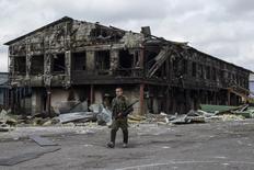 Воюющий на стороне пророссийских сепаратистов мужчина на фоне разрушенного здания завода в городе Нижняя Крынка, Украина 23 сентября 2014 года. Падение промышленного производства Украины, воюющей с пророссийскими сепаратистами на индустриальном востоке, ускорилось до 10,7 процента в 2014 году с 4,3 процента в 2013 году, сообщила предварительные данные Государственная служба статистики. REUTERS/Marko Djurica