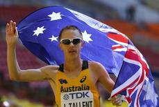 Jared Tallent of Australia holds his national flag as he celebrates finishing third place in the men's 50 km race walk final during the IAAF World Athletics Championships at the Luzhniki stadium in Moscow August 14, 2013. REUTERS/Denis Balibouse