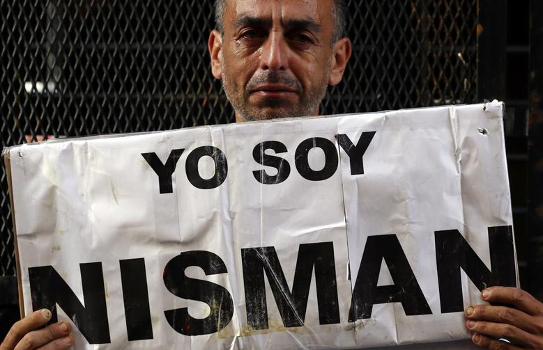 Marcelo Novillo, whose son Adrian was a victim of a violent crime, cries as he holds up a sign that reads ''I am Nisman'' outside the office of the prosecutor who is investigating the death of prosecutor Alberto Nisman in Buenos Aires January 22, 2015.  REUTERS/Marcos Brindicci