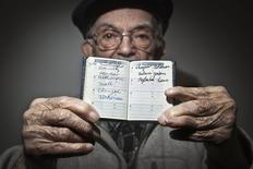 90 year old holocaust survivor Hy Abrams poses for a portrait with a book that he carries with him everyday that documents all the different concentration camps he was held in during the second World War, in the Brooklyn borough of New York January 15, 2015. REUTERS/Carlo Allegri