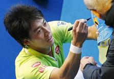 Kei Nishikori of Japan signs autographs after defeating David Ferrer of Spain to win their men's singles fourth round match at the Australian Open 2015 tennis tournament in Melbourne January 26, 2015.   REUTERS/Carlos Barria