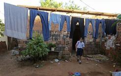 Una niña camina bajo ropa colgada para secar en su casa en Lambare, cerca de Asunción. Imagen de archivo, 2 abril, 2014.  La pobreza afecta a un 28 por ciento de la población de América Latina, un nivel que mantiene desde el 2012, en medio de una desaceleración de la economía de la región, reveló el lunes la CEPAL en un informe. REUTERS/Jorge Adorno