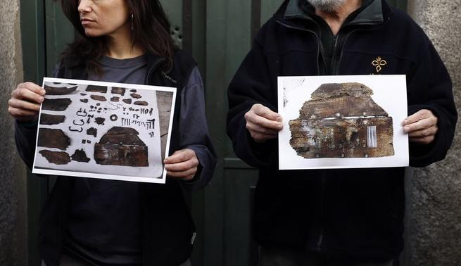 Forensic expert Francisco Etxeberria (R) and archaeologist Almudena Garcia Rubio hold pictures showing the remains of niches, one of them appeared with the letters M.C. on it,  found in the crypt of Trinitarian convent as they pose outside the convent in Madrid January 26, 2015. REUTERS-Sergio Perez