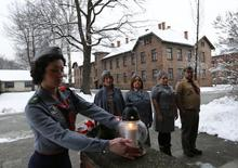 Members of Polish Scouting Association from Canada and U.K. place a lit candle at block 15 in the former Nazi German concentration and extermination camp Auschwitz in Oswiecim January 26, 2015.  REUTERS/Laszlo Balogh