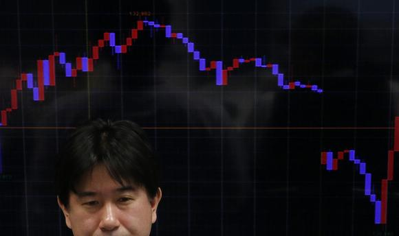 An employee of a foreign exchange trading company stands in front of a monitor, showing the graph of the recent fluctuations of the exchange rates between the Japanese yen against the euro, in Tokyo, January 26, 2015. REUTERS/Yuya Shino