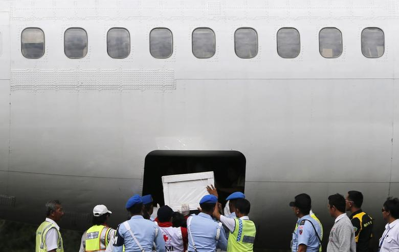 Indonesia soldiers and rescue personnel put a coffin of a passenger of AirAsia Flight QZ8501 into the cargo compartment of a Trigana airplane at Iskandar airbase in Pangkalan Bun, January 27, 2015.  REUTERS/Beawiharta