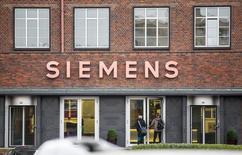 Люди входят в здание Siemens в Берлине 6 ноября 2014 года. Квартальная прибыль промышленных подразделений Siemens снизилась на 4 процента, во многом из-за снижения показателей в энерго- и газовом секторах, где компания пытается бороться с ценовым давлением, а также секторе здравоохранения. REUTERS/Hannibal