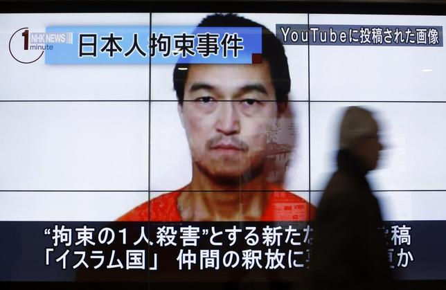 A man walks past screens displaying a television news program showing an image of Kenji Goto, one of two Japanese citizens taken captive by Islamic State militants, on a street in Tokyo January 25, 2015. REUTERS/Yuya Shino