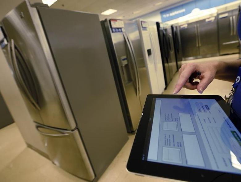An employee uses a touch pad to enter information for a customer shopping  for a refrigerator at a Sears store in Schaumburg, Illinois, near Chicago September 23, 2013. REUTERS/Jim Young