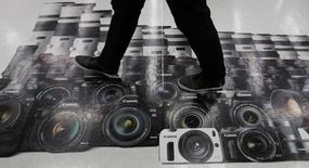 Canon a annoncé mercredi un bénéfice en légère hausse au quatrième trimestre grâce à un yen faible et à de bonnes ventes dans la bureautique même si le groupe japonais a du mal à faire face à la concurrence dans le segment des appareils photo /Photo prise le 27 octobre 2014/REUTERS/Toru Hanai