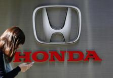 A woman using her mobile phone walks past a Honda Motor Co. logo outside the company's dealership in Tokyo, in this October 28, 2014 file photo.  REUTERS/Yuya Shino/Files