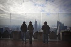 Personas observan los rascacielos de Manhattan en Nueva York. Imagen de archivo, 15 enero, 2015. El crecimiento económico de Estados Unidos se desaceleró con fuerza en el cuarto trimestre, ya que un débil gasto empresarial y un déficit comercial mayor contrarrestaron el más intenso ritmo del gasto del consumidor desde el 2006. REUTERS/Carlo Allegri