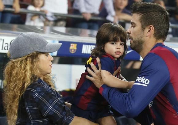 Singer Shakira (L) passes their son Milan to Barcelona's Gerard Pique before the Spanish first division soccer match between Barcelona and Eibar at Camp Nou stadium in Barcelona in this file photo taken on October 18, 2014. REUTERS/Albert Gea