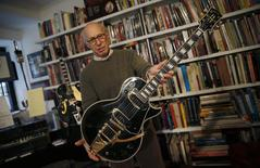 "Guernsey's Auctions President Arlan Ettinger holds the Les Paul guitar known as ""Black Beauty"", which will go up for auction next month, in New York January 29, 2015. REUTERS/Mike Segar"